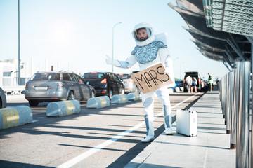 Trip to mars. Spaceman wearing strange armor is catching car. Full length portrait. Copy space on left side