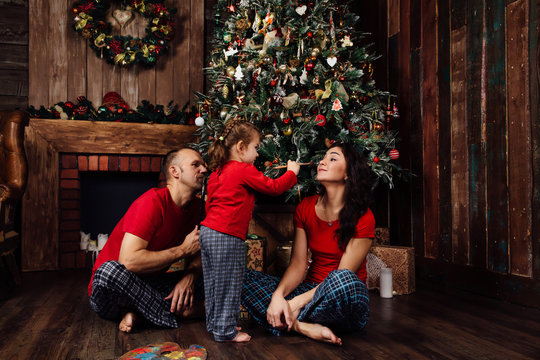 The family in pajamas plays next to a Christmas tree and a fireplace.