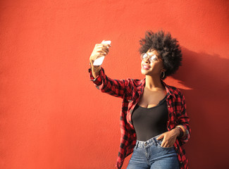Cool girl making a selfie in front of a red wall