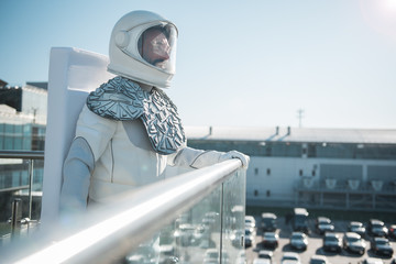 Cheerful spaceman wearing white armor is standing outside and looking forward with sincere smile. Profile. Copy space on right side