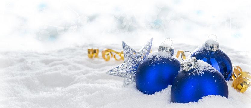 Weihnachten, Weihnachtskugeln und Geschenkband im Schnee vor hellem Hintergrund mit Bokeh, Panorama