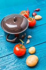 Photo of iron pot, tomato, potato, onion