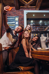 Handsome young guy taking selfie with a group of pretty girls having dinner in trendy restaurant