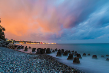 Long exposure photo of the concrete conical boulders lying in the sea on the background of coastline of Sochi at dawn, Russia