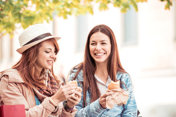 Two young female friends laugh and eat sandwich outdoors.