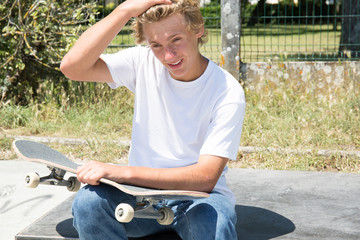 blond boy sit on floor with teenager skateboard on hands