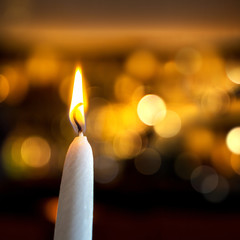 Candles light, bright background for the New Year greeting card with golden bokeh