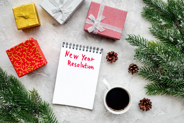 New year resolution. Notebook among gift boxes and spruce branch on grey stone background top view