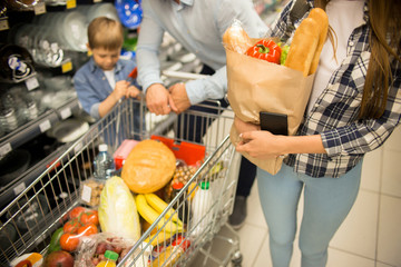 High angle portrait of happy young family with child shopping for groceries in supermarket together, smiling while pushing shopping cart in aisle