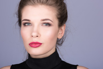 Closeup portrait of a beautiful young woman with light makeup and red lipstick