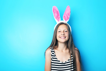 Portrait of beautiful girl with rabbit ears on blue background