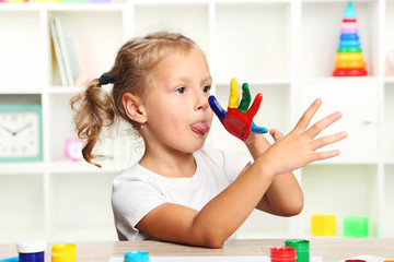 Beautiful little girl with colourful painted hands
