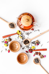 Tea party set. Tea pot, cups, dried tea leaves, fllowers, spices on white background top view