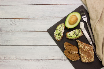 Avocado  sandwiches with cottage cheese and whole wheat bread. Healthy breakfast served on black stone board ,white wooden table.Space for text