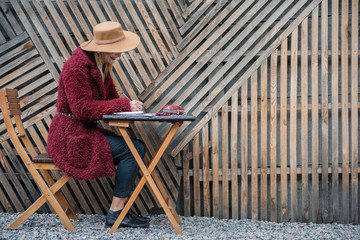 Side view of inspired blond girl writing her thoughts in diary. She is sitting at table near wooden fence and laughing. Copy space in right side