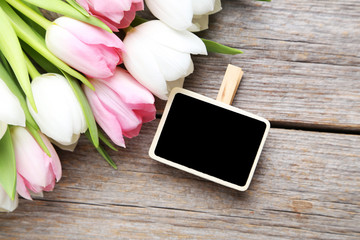 Bouquet of tulips with frame on grey wooden table