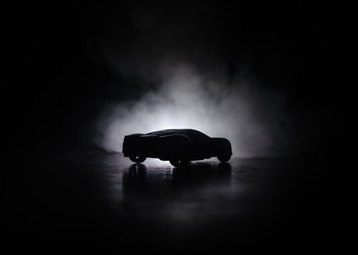 The car in the shadows with glowing lights in low light, or silhouette of sport car dark background