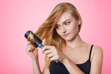 Portrait of female model combs her light straight hair, going to have date with boyfriend, cares about her hair, prepares to make trendy hairstyle, isolated over pink background. People, beauty, care