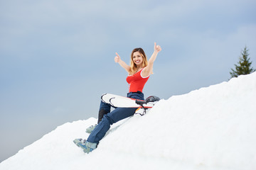 Smiling woman skier wearing ski pants and red bodice, showing thumbs up, sitting on the top of the snowy slope with skis at winter ski resort in the mountains copyspace active seasonal extreme concept