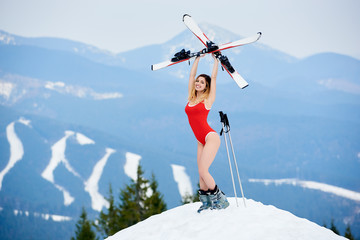 Active woman skier wearing bodice, holding skis above head, standing on the top of the slope at ski resort. Mountains, forests and ski slopes on the background. Ski season and winter sports concept