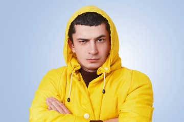 Portrait of serious brunet hipster guy keeps hands crossed, wears fashionable yellow raincoat with hood, listens attentively to interlocutor, doesn`t agree with something, tries to speak his mind
