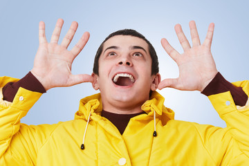 Joyful smiling excited brunet man wears yellow anorak gestures actively, looks happily up, notices something pleasant on ceiling, isolated over blue background with copy space for your text.