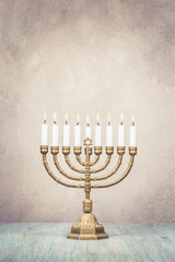Bronze Hanukkah menorah with burning candles on wooden table front old vintage concrete wall background. Holiday greeting card concept. Retro style filtered photo