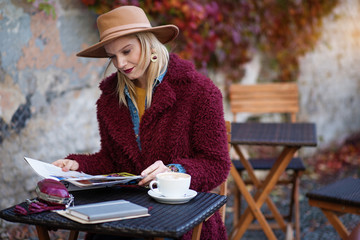 Portrait of calm young woman is reading magazine with interest. She is sitting in cafeteria outdoor in autumn weather. Cup of coffee on table. Copy space