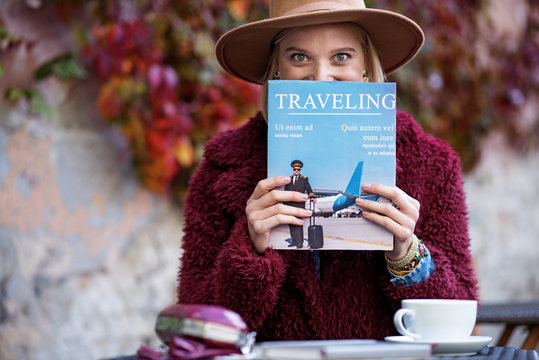 I am fold of traveling. Cheerful blond girl is holding magazine near her face and looking at camera with excitement. She is sitting at table in cafe outside