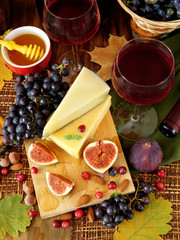 Parmesan on a board surrounded by figs, grapes and honey. Ingredients for a cheese plate