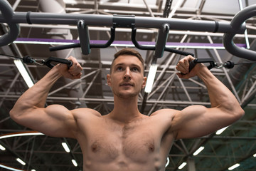 Low angle portrait of shirtless muscular man pulling up on bar during workout in modern gym