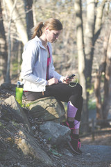 Female fitness model outside on a warm day and listening to music using smart phone.