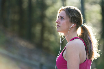 Fresh, attractive young fitness woman in sports clothes on nature trail.