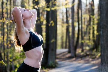 Fit woman in sports bra stretches on nature trail.