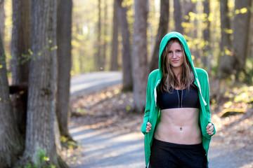 Happy fit woman outside in nature wearing sport bra and sweatshirt