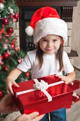 Happy little girl in Santa hat holding red gift box for Christma