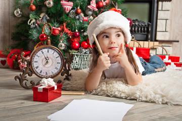 Dreaming little girl in Santa hat writes letter to Santa Claus