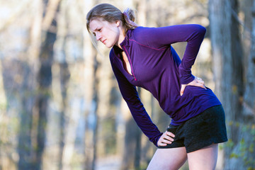 Woman in fitness clothing on nature trail experiencing back pain while exercising