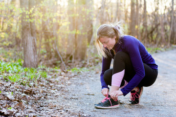 Young fitness woman runner tying shoelace in nature trail at sunset