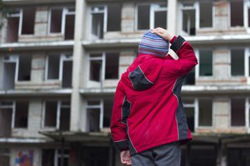 Ребенок в красной куртке смотрит на заброшенное здание