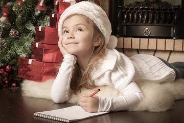 Funny girl in Santa hat writes letter to Santa near christmas tr