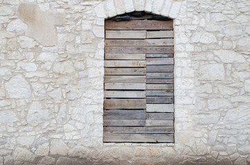 Facade of an abandoned old stone limestone house with boarded up window, copy space