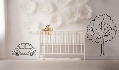 White bedroom with crib and decorated wall