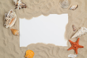 Seashells on sand with white paper in center