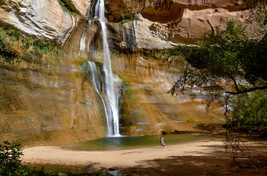 girl standing near plunge pool at the bottom of Lower Calf Creek falls  Grand Staircase - Escalante National Monument, Utah