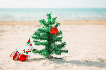 christmas tree, red christmas balls and snowman on the beach