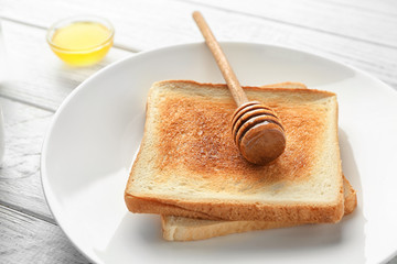 Plate with tasty toasts and honey dipper on wooden table