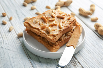 Plate of tasty toasts with peanut butter on wooden table
