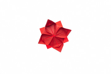 Lotus flower origami on white. Beautiful and simple model, folded red paper. Handmade ornaments, DIY, children's art.