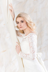 fashionable gown, beautiful blonde model, bride hairstyle and makeup concept - charming young woman in wedding white dress standing indoors on light background, slim girl posing near curtains
